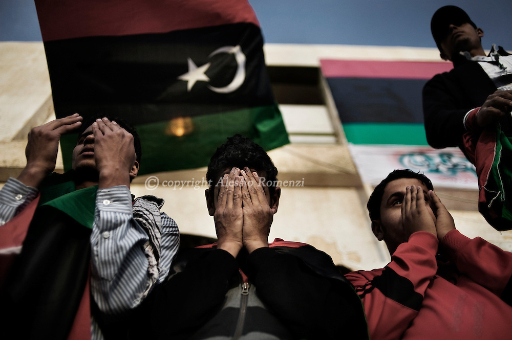 LIBYA, Tobruk : Libyan anti-government protesters pray at the end of a small demonstration in the eastern Libyan city of Tobruk on March 14, 2011 as Moamer Kadhafi's forces bombarded rebel positions on the doorstep of Ajdabiya, a key town which the revolution against his rule has vowed to defend at all costs.ALESSIO ROMENZI