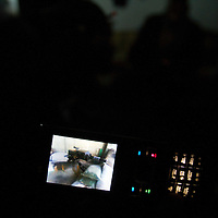 Free Syrian Army soldiers look at videos and photos of sniper attacks in Al Janoudiyah during a power cut. Janoudia, Syria