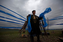 Mongolian Shaman Gankhuyag Batmunkh holds up blue colored scarves, symbolic of the 'open sky' or 'Tengri', during a  Shaman ceremony by an 'ovoo' or 'sacred stone' site on Black Mountain Head in Nalaikh district of Ulan Bator in Mongolia, 06 July 2012. The Shaman ceremony is held for a family to give offerings to the spirits of nature and to bring good karma to the members of family.  The scarves of color blue is symbolic of the 'open sky' or 'Tengri' while red represents 'fire'; orange for 'sand' and white for 'milk'. Shamanism comes from the term 'shamans' that refers to priests or mediums that acts as vessels for spirits, gods and demons to communicate with the human world. In Mongolia, they adhere to the ancient beliefs of Tengrism, where spirits live in all of nature, in the sun, moon, lakes, rivers, mountains, and trees.