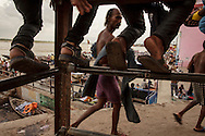 Hindu pilgrim coming out of the water after bathing in the Ganges River at Dashashwamedh Gath in Varanasi, India.