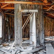 """Dilapidated doors and interior of a ramshackle building at Bodie, California's official state gold rush ghost town. Bodie State Historic Park lies in the Bodie Hills east of the Sierra Nevada mountain range in Mono County, near Bridgeport, California, USA. After W. S. Bodey's original gold discovery in 1859, profitable gold ore discoveries in 1876 and 1878 transformed """"Bodie"""" from an isolated mining camp to a Wild West boomtown. By 1879, Bodie had a population of 5000-7000 people with 2000 buildings. At its peak, 65 saloons lined Main Street, which was a mile long. Bodie declined rapidly 1912-1917 and the last mine closed in 1942. Bodie became a National Historic Landmark in 1961 and Bodie State Historic Park in 1962."""