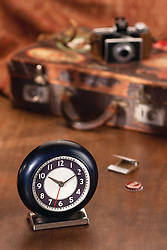 Vintage Travel Vignette containing a vintage clock, suitcase, and folding camera.  Generic matches and a cola bottle cap complete the scene