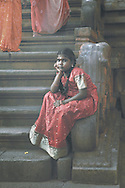 A girl wearing a red sari waits for her parents on the steps of a Hindu temple, Thanjavur, Tamil Nadu, India.