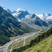 "The icy Bernina Range rises above Ova da Roseg river valley, near Pontresina, Switzerland, in the Bernina Alps, Europe. Tschierva Glacier flows from the peaks clustered on left: Piz Scerscen (3971 m) and Piz Roseg (3937 m/12,917 ft). At right (west), Roseg Glacier flows from Piz Glüschaint (3594 m). Val Roseg is in the Swiss canton of Graubünden (or Grisons / Grigioni / Grischun); the lower Roseg Valley is in Pontresina, whereas the upper valley is in an exclave of Samedan Municipality. Hike from Pontresina up Roseg Valley to Fuorcla Surlej for stunning views of Piz Bernina and Piz Roseg, finishing at Corvatsch Mittelstation Murtel cable car. Walking 14 km, we went up 1100 meters and down 150 m. Optionally shorten the hike to an easy 4 km via round trip lift. The Swiss valley of Engadine translates as the ""garden of the En (or Inn) River"" (Engadin in German, Engiadina in Romansh, Engadina in Italian), and is part of the Danube basin."