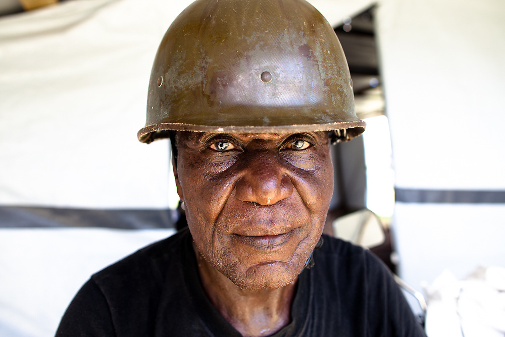 Sergeant Rene Louis, age 67, wears his helmet that was given to him when he first joined the Haitian army in 1964. Louis is now training new recruits in the army. Though not yet officially recognized by the government, the defunct Haitian army is gathering in training camps across Haiti. The army was disbanded in 1995 by Jean Bertrand Aristide with the help of the U.S. and UN after the the army successfully overthrew Aristide in a coup in 1994. Army veterans who feel they must pass their knowledge on to the next generation are behind the trainings. They believe they have the support of president elect Michel Martelly, who is known to have close ties with many former army officials and who has promised to reinstate the army. This group just a few miles south of Port-au-Prince began training in March, 2010 and their numbers have since grown to more than 800.