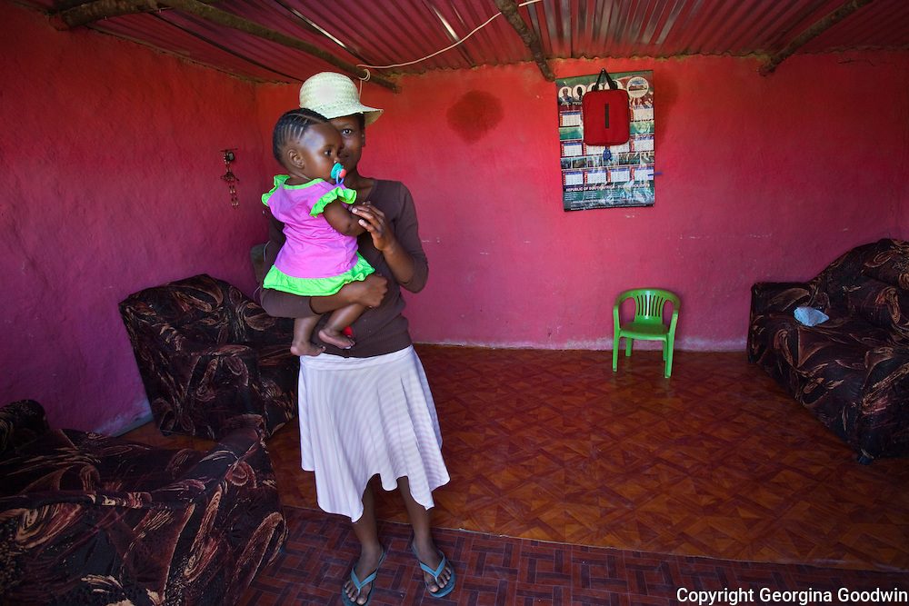 18 year old Fundi with her 6 month old daughter Rina in their family home in the Drakensburg Mountains one and a half hours drive inland from the sea town of Durban in KwaZulu Natal, South Africa. December 2010