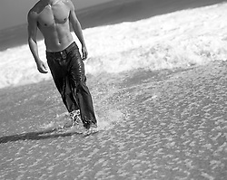 detail of a lean shirtless man in jeans coming out of the ocean