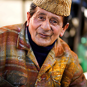 A bus painter sits in the bus yards of Baramulla, Kashmir in his multicolored coat.