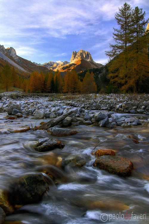 The Valle Stretta is a small, narrow valley in the Western Alps, right at the border between Italy and France. It's certainly one of the best alpine environment I know: evergreen forests, small glacial lakes, rivers and small streams, waterfalls. And, as the ice on the cake, the amazing jagged peak known as Grand Seru, part of the Mount Thabor massif, dominate the valley at his top. I took this picture on a evening of mid October, the period when fall colours in the valley reach their peak.