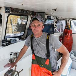 """Captain Matt Clemmons in the wheelhouse of """"Mean Kathleen"""" at Potts Harbor Lobster in Harpswell, Maine."""