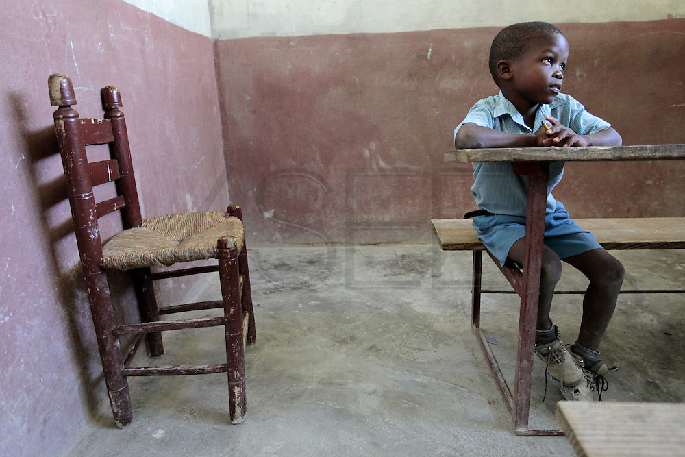A kindergarten student pays attention to the lesson at the Church of Christ school in Saint Roch mountain above Carrefour, Haiti.  The classes are conducted in a concrete building with a concrete floor.  The 6th grade is conducted in the church. With no public schooling, parents are forced to solicit help from foreigners who sponsor their children's schooling.
