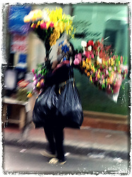 Vendor walks along the street with an abundance of colorful flower bouquets, Hanoi, Vietnam, Southeast Asia