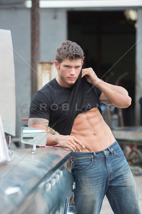 very good looking muscular auto mechanic with grease and dirt on his face lifting his shirt up to show his abs