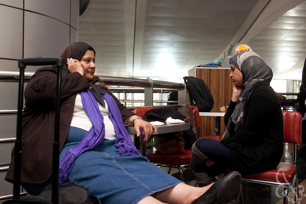 Salma Khalil, 20, (r) a student at the American University in Cairo (AUC) waits for a flight with her mother Rasha al-Khodary at the Cairo International airport for word of available flights out of the country January 30, 2011 in Cairo, Egypt. Many Egyptians like Khalil are desperate to flee the country following nearly a week of ongoing unrest that threatens to bring down President Hosni Mubarak's regime.