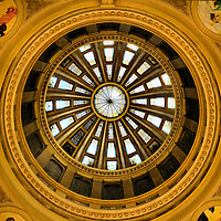 South Dakota Capitol Rotunda Dome in Pierre, South Dakota<br /> The eye travels 96 feet from the glass and tile rotunda floor to the top of the South Dakota Capitol dome in Pierre. Edward Simmons painted four pendentives (dome arches) like he had for the Minnesota Capitol five years before. The south one in the upper left is called &ldquo;Motherhood.&rdquo;  The other shows goddess Minerva as &ldquo;Wisdom, Industry and Mining.&rdquo; The next stop is a band of ribbons symbolizing government&rsquo;s eternity. Next are 16 painted alcoves followed by rectangular openings and Victorian stained glass all in a hub and spoke design. It is gorgeous!