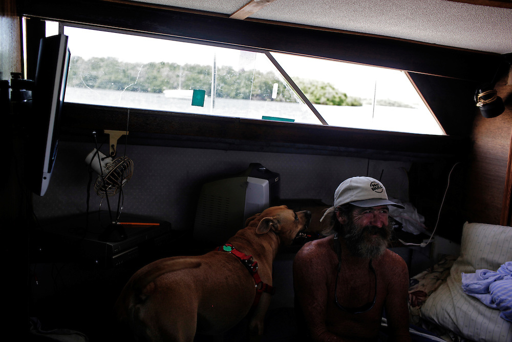 Randy Eibler relaxes below deck talking with Scot Janikula as his dog Renegade, joins them to get out of the sun for a few minutes. Living in Estero Bay near the north end of Fort Myers Beach, the water is generally calm, but can get choppy during passing thunderstorm.