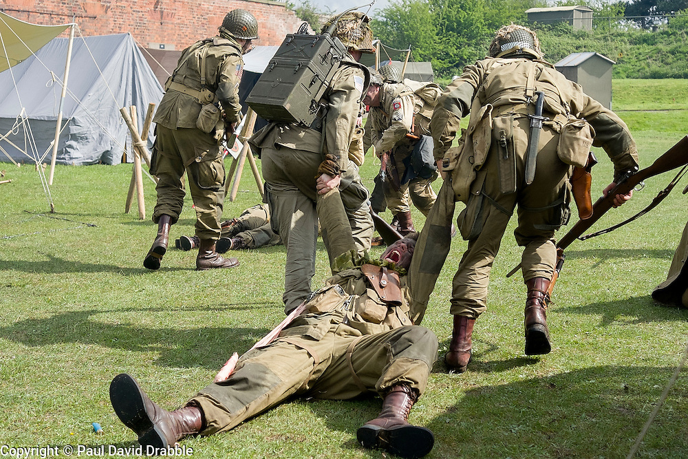 Members of the US 82nd Airborne/505th RCT living History Group take part in the first days battle re-enactment at Fort Paull. Reenactors pulling a &quot;casualty&quot; off the field as the Americans are pushed back <br /> <br />   03 May 2015<br />   Image &copy; Paul David Drabble <br />   www.pauldaviddrabble.co.uk