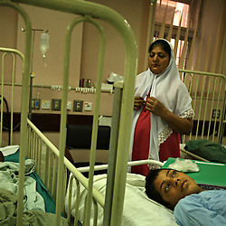 A young boy waits for surgical treatment at the Children's Hospital at the Pakistan Institute of Medical Sciences in Islamabad, Pakistan, Sept. 18, 2007.