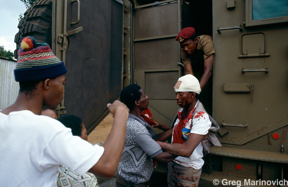 Bekkersdal Township, South Africa, Feb 1994: Soldiers of the SADF attend to an injured m,an during three way clashes between security forces, ANC members and  AZAPO supporters in the far West Rand township of Bekkerdal, South Africa.