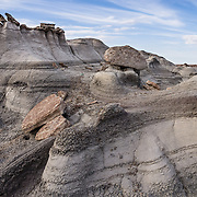 Eroded badlands of Bisti/De-Na-Zin Wilderness, south of Farmington, in San Juan County, New Mexico, USA. This fantasy world of strange rock formations is made of interbedded sandstone, shale, mudstone, coal, and silt. These rock layers have weathered into eerie hoodoos (pinnacles, spires, and cap rocks). This was once a riverine delta west of an ancient sea, the Western Interior Seaway, which covered much of New Mexico 70 million years ago. Swamps built up organic material which became beds of lignite. Water disappeared and left behind a 1400-foot (430 m) layer of jumbled sandstone, mudstone, shale, and coal. The ancient sedimentary deposits were uplifted with the rest of the Colorado Plateau, starting about 25 million years ago. Waters of the last ice age eroded the hoodoos now visible. The high desert widerness of Bisti is managed by the US Bureau of Land Management (BLM).