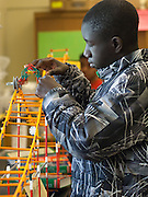 Seattle, Washington: June 15, 2012. In science class at Seattle World School, African immigrant student tests the race car he built while learning about gravity and kinetic energy.
