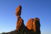 Balanced Rock, a prominent feature of Arches National Park near Moab, Utah, is turned red by the golden light of sunrise. The balanced rock is a cap rock that is 55 feet (17 meters) tall and makes up nearly half the overall height of the formation. The formation is made up of several layers of sandstone, which erode at different rates; the layer between the cap rock and the pedestal erodes at a much faster rate than the others.