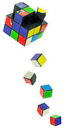 Broken Rubiks Cube puzzle surrounded by detached colorful individual cubes many of which have damaged surfaces on a white background for a game of intellect and skill