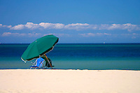 10 September 2001: North Point  beach on Nantucket, Cape Cod, MA. A lone beach chair and umbrella sit in the white sand on shore from the blue green water and blue skies. Scenic travel view. Stock photo.<br />
