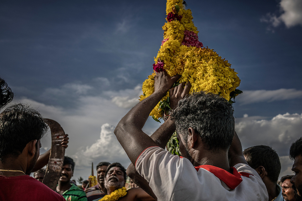 Men carry an idol coated with flowers from the beach back, with two village men deep a trance (one is bottom center) to the local Hindu trance as part of the Ganesh Chaturthi Festival.  Tiruchchepuram, Tamil Nadu, India.