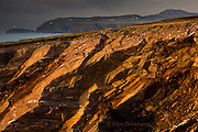 South Stack lighthouse flashes in bad weather as sunshine lights orange sedimentary cliffs near South Stack, Holy Island, Anglesey, Wales