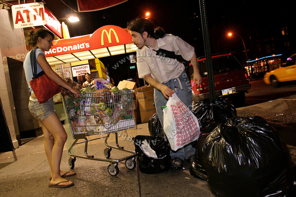 Adam, 28, (right) one of the founders of the Freegan community in New York, and Stephanie, 21, a member looking for edible food on a dump site along 3rd Avenue in Manhattan, New York, NY., on Wednesday, July 5, 2006.Freegans are a community of people who aims at recovering wasted food, books, clothing, office supplies and other items from the refuse of retail stores, frequently discarded in brand new condition. They recover goods not for profit, but to serve their own immediate needs and to share freely with others. According to a study by a USDA-commissioned study by Dr. Timothy Jones at the University of Arizona, half of all food in the United States is wasted at a cost of $100 billion dollars every year. Yet 4.4 million people in the United States alone are classified by the USDA as hungry. Global estimates place the annual rate of starvation deaths at well over 8 million. The massive waste generated in the process fills landfills and consumes land as new landfills are built. This waste stream also pollutes the environment, damages public health as landfills chemicals leak into the ground, and incinerators spew heavy metals back into the atmosphere. Freegans practice strategies for everyday living based on sharing resources, minimizing the detrimental impact of our consumption, and reducing and recovering waste and independence from the profit-driven economy. They are dismayed by the social and ecological costs of an economic model where only profit is valued, at the expense of the environment. In a society that worships competition and self-interest, Freegans advocate living ethical, free, and happy lives centred around community and the notion that a healthy society must function on interdependence. Freegans also believe that people have a right and responsibility to take back control of their time.