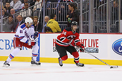 Oct 21, 2014; Newark, NJ, USA; New Jersey Devils center Adam Henrique (14) skates with the puck past New York Rangers left wing Rick Nash (61) during the second period at Prudential Center.