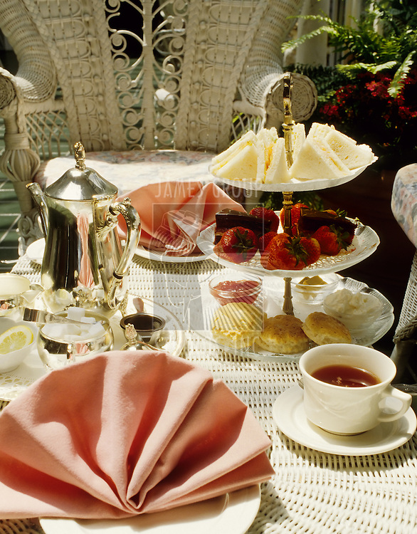 High tea in a garden setting on white wicker furniture