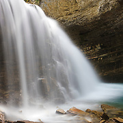An unamed waterfall plunges into a narrow passage in Johnston Canyon in Banff National Park, Alberta, Canada.