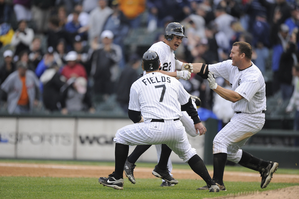 CHICAGO - JUNE 11:  Scott Podsednik #22 of the Chicago White Sox is mobbed by teammates Josh Fields #7 (L) and Jim Thome #25 (R) after hitting a game winning single in the ninth inning against the Detroit Tigers on June 11, 2009 at U.S. Cellular Field in Chicago, Illinois.  The White Sox defeated the Tigers 4-3.  (Photo by Ron Vesely)