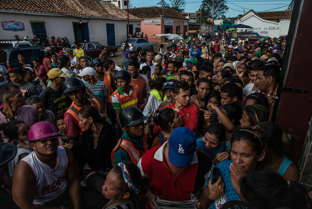 """LA VELA, VENEZUELA - SEPTEMBER 27, 2016: Hundreds of Venezuelans lined up in front of a grocery store in La Vela to wait to see if government price-controlled food would be delivered. Despite having the largest known oil reserves in the world, Venezuela is suffering from hyperinflation and a severe economic crisis making affordable food difficult for most middle and working class families to access.  Well over 150,000 Venezuelans have fled the country in the last year alone, the highest in more than a decade, according to scholars studying the exodus. As Hugo Chávez's Socialist-inspired revolution collapses into economic ruin, as food and medicine slip further out of reach, the new migrants include the same impoverished people that Venezuela's policies were supposed to help. """"We have seen a great acceleration,"""" said Tomás Paez, a professor who studies immigration at the Central University of Venezuela. He says that as many as 200,000 Venezuelans have left in the last year, driven by how much harder it is to get food, work and medicine — not to mention the crime such scarcities have fueled.  PHOTO: Meridith Kohut"""