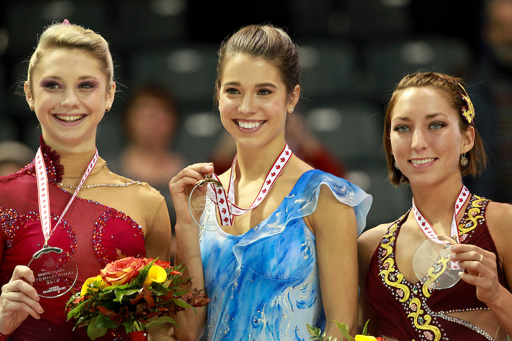 20101030 -- Kingston, Ontario -- Gold medalist Alissa Czisny of the United States, centre, poses for photographers with Ksenia Makarova of Russia, left, the silver medalist and bronze medalist Amelie Lacoste of Canada during the medal ceremony for the ladies competition at Skate Canada International in Kingston, Ontario, Canada, October 30, 2010. <br /> AFP PHOTO/Geoff Robins