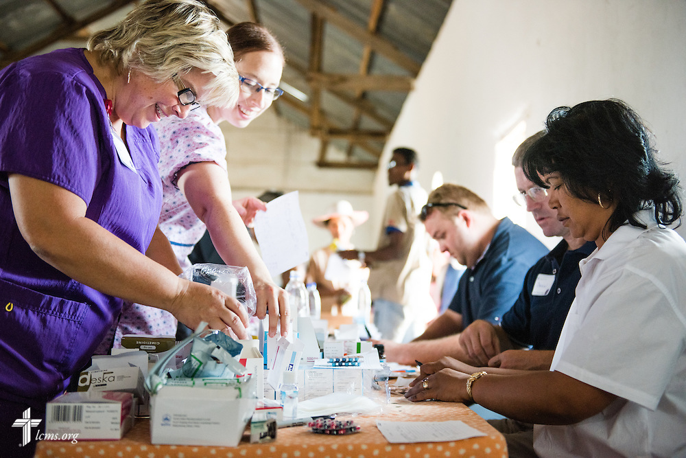 (L-R) Lea Keesee, Kimberly Pepmiller, Jacob Fiene, Daniel Christiansen, and Domoina Razoanivelo Andriamanisa fill prescriptions at the Mercy Medical Team clinic on Saturday, Oct. 18, 2014, at a Fiangonana Loterana Malagasy (FLM) Lutheran church in Antsoantany, Madagascar. LCMS Communications/Erik M. Lunsford