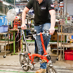 London, UK - 29 January 2013: CEO Will Butler-Adams poses for a portrait with an orange bike in the Brompton Bicycles factory in South West London. The company was founded in 1976 by Andrew Ritchie and is one of only two major frame manufacturers still based in the UK. Today, Bromptons are sold in 42 export markets.
