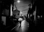 """Homeless on streets / Streets like a nursing home: Destitute senior walks the street in San'ya on a rainy winter night empty but for the occasional old man returning to a cheap """"do-ya"""" boarding house.  Tokyo, Japan.  Do-ya have become de facto dumping grounds for unwanted old men.  In the northeast of Tokyo is a community that used to be called San'ya, where the unwanted lower Japanese castes of butchers and leather tanners had to live.  Now it is known for low cost  boarding houses.  Though San'ya is thought of as a refuge for alcoholics, peel back a thin veneer and it immediately becomes evident what San'ya really is, a repository for unwanted, unloved old men.  Many do-ya are little more than unregistered nursing homes, minus the medical staff.  It keeps those, who can afford the Y1,000 - Y2,000/night off the streets at night."""
