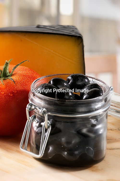 Close-up view of jar with pitted black olives, ripe tomato and chunk of cheese with black wax coating on a kitchen table.
