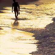 Surfer walking and carrying his board across the yellow sun reflecting waterline at sunset at Jobos Beach, Isabela, Puerto Rico, Playa Jobos