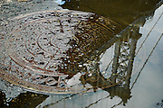 Reflection of the Manhattan Bridge on part of a manhiole covered by a puddle in DUMBO, Brooklyn, New York, 2008.