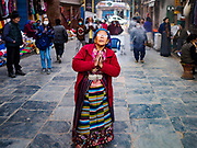 16 MARCH 2017 - KATHMANDU, NEPAL: A woman prays as she enters the complex of Boudhanath Stupa in Kathmandu. The stupa is the holiest site in Nepali Buddhism. It is also the center of the Tibetan exile community in Kathmandu. The Stupa was badly damaged in the 2015 earthquake but was one of the first buildings renovated.      PHOTO BY JACK KURTZ