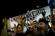 Tens of thousands of people gather around Syntagma square. A Greek Orthodox priest is seen on the megaphone denouncing the governments move to accept the new austerity measures, Athens, Greece. Image © Angelos Giotopoulos/Falcon Photo Agency
