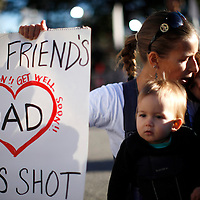 """Susan Shobe (C) sings """"Let There Be Peace on Earth"""" with her children Violet Schorr, 1, (L) and Willow Schorr, 3, (R) as she knelt at a memorial outside the hospital where victims of the shootings are recovering in Tucson, Arizona January 10, 2011.  Shobe's best friend's father Ron Barber was shot in the attack. Barber, district director for congresswoman Gabrielle Giffords spent more than six hours in surgery January 8 after being shot twice during the shootings that left six people dead.  REUTERS/Rick Wilking (UNITED STATES)"""