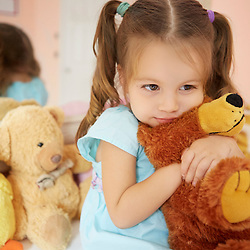 Portrait photograph of young girl holding teddy bear
