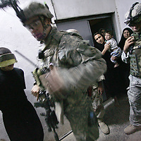 Family members cry out as a US soldier with the 2/9 Cavalry, 3rd Brigade, 4th Infantry Division, walks past a man detained for suspected involvement in sectarian violence in the village of Abu Sayda in Diyala province, northeast of Baghdad. The man at far right is an Iraqi soldier. The man 2nd from right is an Iraqi translator working for the US. US and Iraqi Army soldiers conducted an overnight sweep through this mainly Shia neighborhood looking for individuals suspected of committing sectarian violence in the area. October 2006.