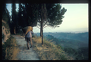 Early morning in Tuscany, an old man carrying a bag on his back. Kodachrome