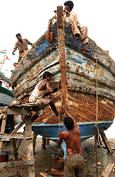 Fishing families  in Nagapattinum district in Tamil Nadu, India  repairs boats  September ,2005. The recovery process is slow and the situation still grim for many of the worlds poorest who were most affected by the deadly wave.  (Ami Vitale)
